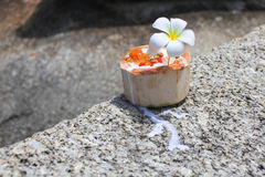 Ice cream on summer coconut with orchid flower. On the tropical beach with people blurred behind Stock Photography