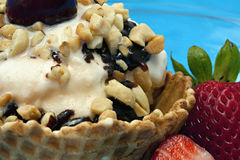 Ice Cream Sundae. Close up of Vanilla Ice Cream Sundae in an edible waffle bowl with chocolate syrup, nuts, strawberries on the side, and a cherry on top Royalty Free Stock Images
