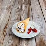 Ice cream sundae on grey wooden background. Ice cream with red currant in a waffle cone on wooden background Stock Image