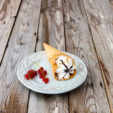 Ice cream sundae on grey wooden background. Ice cream with red currant in a waffle cone on wooden background Royalty Free Stock Photos
