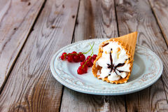 Ice cream sundae on grey wooden background. Ice cream with red currant in a waffle cone on wooden background Stock Photo