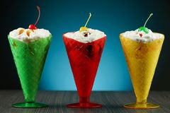 Ice cream sundaes. A trio of ice cream sundaes in colourful glasses with cherries on top stock images