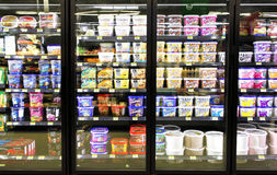 Ice cream in supermarket. Different brands and flavors of ice cream on fridge shelves in a supermarket Stock Images