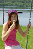 Ice cream on a swing. Girl eating ice cream while sitting on a swing Royalty Free Stock Images