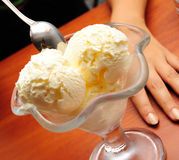 Ice cream and tea. Close-up of ice cream and hand, shallow DOF Royalty Free Stock Images