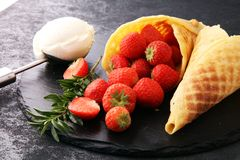 Ice cream vanilla flavor and cones with fresh strawberry setup o Stock Photo