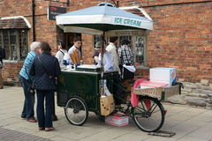 Ice cream vendor with cart. And customers in street Royalty Free Stock Photo