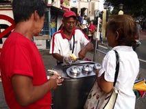 An ice cream vendor prepares an ice cream sandwich for a customer. Stock Image