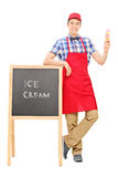 Ice cream vendor standing by a blackboard Royalty Free Stock Image