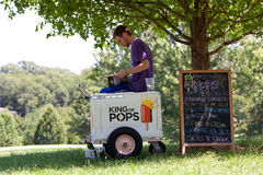 Ice Cream Vendor Waits For Customers In Park. Atlanta, GA, USA - July 28, 2012:  An unidentified ice cream vendor reads a book to pass the time as he waits for Royalty Free Stock Photography