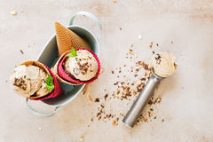 Ice cream in wafer cones. Creamy  ice cream in wafer cones served in vintage metal bowl with spoon over rustic surface.  Top view, blank space Royalty Free Stock Image