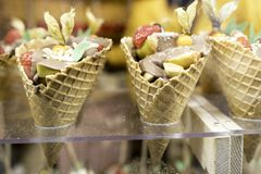 Ice cream in waffel cone with fruits a sweet treat for anyone. After dinner or street food, ice-cream cones crunchy and decorated with fruits a healthy twist to royalty free stock photo