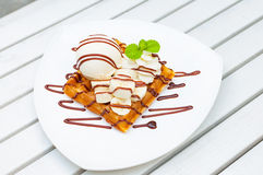 Ice cream waffle banana with chocolate sauce and mint leaf decor Stock Photography