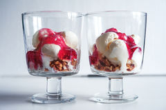 Ice cream with walnuts and raspberry jam in a glass. Ice cream ball with walnut Royalty Free Stock Photo