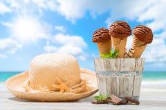 Ice Creams At The Beach. Chocolate flavor ice creams with sunhat and beach blur background Stock Photos