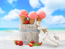 Ice Creams On Vacation. Strawberry fruit ice creams with nautical anchor and beach blur background Stock Photo