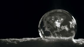 Ice crystal ball freezing on snow on black background stock footage