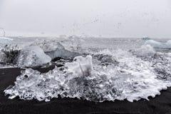 Ice crystal on famous black sand beach and ocean waves, a part of icebergs from Jokulsarlon glacier lagoon, Diamond beach, Iceland. Ice crystal on the famous stock photography