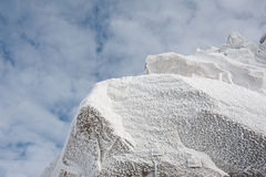 Ice crystals formed on rockface in winter against cloud sky Stock Photos
