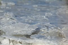 Ice crystals on the river in the afternoon on a blue background stock photo