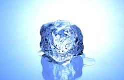 Ice Cube. Melting ice cube on blue reflective surface Stock Images