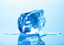Ice cube. Melting ice cube with blue toning in background Stock Images