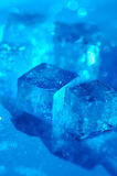 Ice cube. With a blue background royalty free stock photos