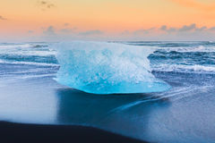 Ice cube on black volcano sand beach Stock Images