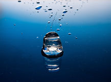 Ice cube on blue surface Royalty Free Stock Photos