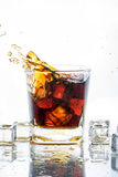 Ice cube droped in cola glass and cola splashing Stock Photo