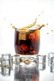 Ice cube droped in cola glass and cola splashing Royalty Free Stock Photo