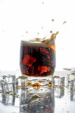 Ice cube droped in cola glass and cola splashing Royalty Free Stock Image