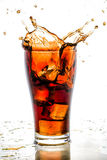 Ice cube droped in cola glass and cola splashing Stock Images