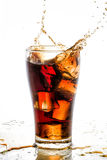 Ice cube droped in cola glass and cola splashing Stock Photos