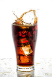 Ice cube droped in cola glass and cola splashing Stock Photography