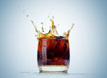 Ice cube droped in cola glass and cola splashing Stock Image
