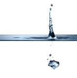 Ice-cube is dropped into clear water Royalty Free Stock Photography