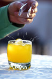 Ice cube dropped into the glass of juice Royalty Free Stock Photography