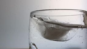 Ice cube fall into glass of water stock video footage