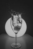 Ice cube falling in glass. Ice cube falling in wine glass / black white Royalty Free Stock Photos