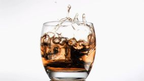 Ice cube falling in super slow motion in scotch stock footage