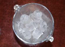 Ice cube in a glass bucket on a wooden table. stock photos