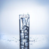 Ice cube makes splash into glass of water Royalty Free Stock Photos