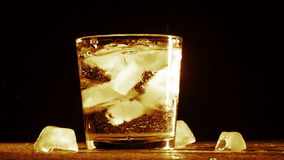 Ice cube splash in glass water isolated on black stock footage