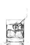 Ice cube splashing in a cool glass of water Stock Image