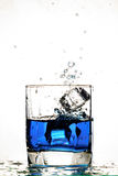 Ice cube splashing in a cool glass of water Stock Photos