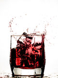 Ice cube splashing in a cool glass of water Royalty Free Stock Photography