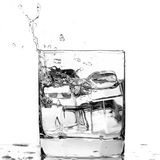 Ice cube splashing in a cool glass of water Royalty Free Stock Photo