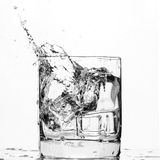 Ice cube splashing in a cool glass of water Royalty Free Stock Images