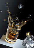 Ice cube splashing into a glas of liquid. Royalty Free Stock Images